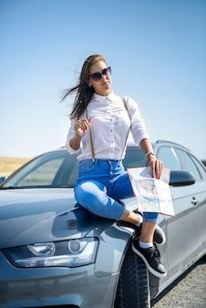 Bella mappa vista donna per il viaggio. bella ragazza in piedi accanto alla macchina. il piacere di viaggiare