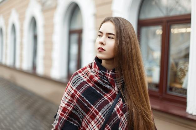 Bella donna in una sciarpa a righe vintage sulla strada
