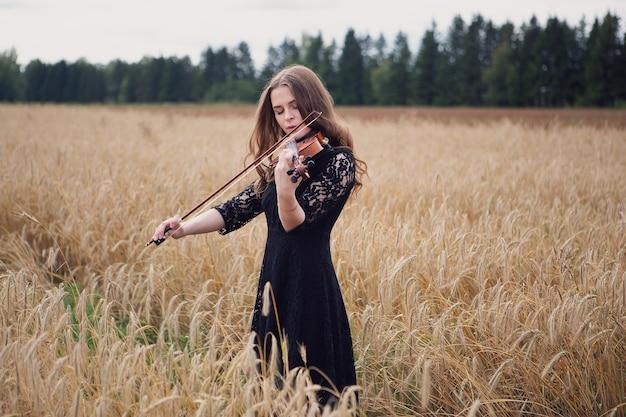 Bella donna violinista gode di suonare il violino sulla maturazione del campo di grano