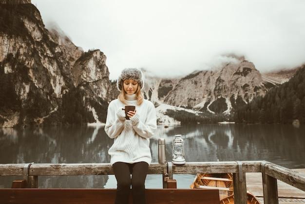 Bella donna che visita un lago alpino a braies, italia