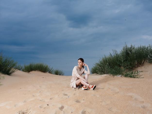 La bella donna cammina lungo lo stile elegante dei tropici della sabbia della spiaggia