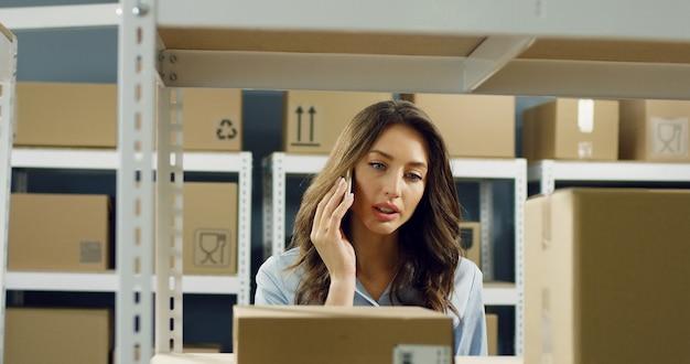 Bella donna che cammina nel negozio di ufficio postale a scaffali con pacchi di cartone e parlando sul telefono cellulare. operaio femminile che parla sullo smartphone.