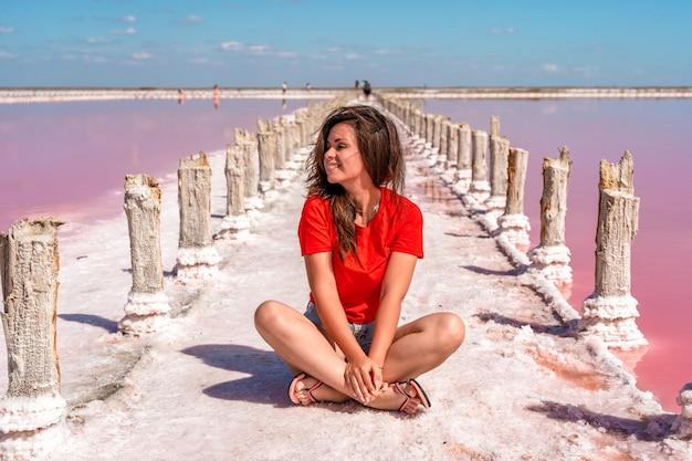 Una bella donna cammina su una spiaggia salata tra bastoncini di legno su un lago rosa salato con un cielo blu