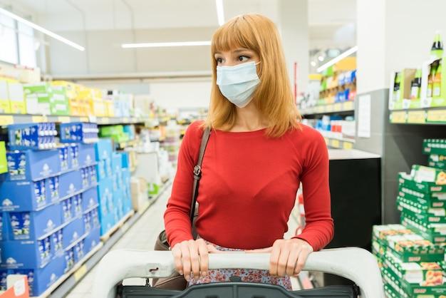 Carretto ambulante della tenuta della maschera di protezione d'avvertimento della bella donna. shopping al blocco della quarantena pandemica al supermercato. concetto di coronavirus