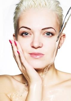 Bella donna che lava il suo fronte
