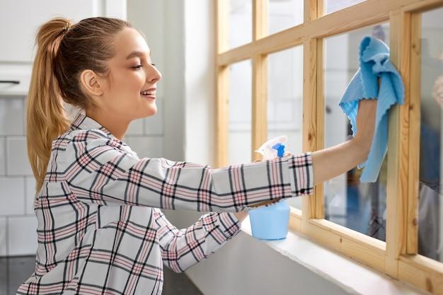 Bella donna che lava la finestra con la finestra di pulizia dello straccio di spugna che pulisce lo sporco