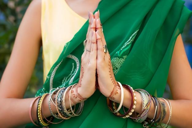 La bella donna indossa le mani tradizionali del vestito da sari verde arabo arabo musulmano tradizionale con gioielli e bracciali con motivo mehndi tatuaggio henné. incrociò le mani in preghiera di meditazione. concetto di religione.