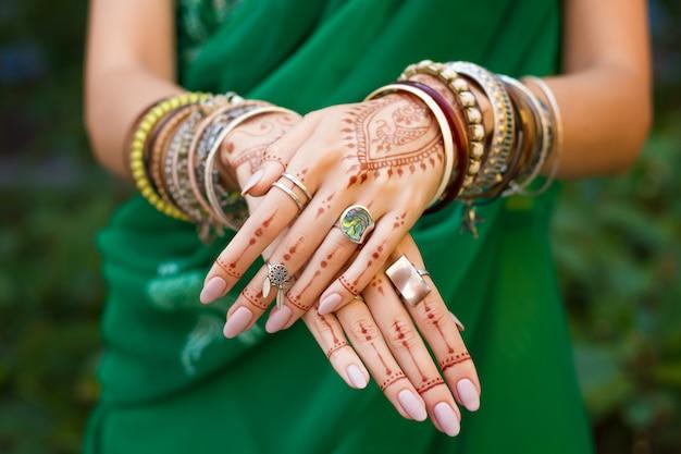 La bella donna indossa le mani tradizionali del vestito da sari verde arabo arabo musulmano tradizionale con gioielli e bracciali con motivo mehndi tatuaggio henné. concetto felice di celebrazione di festival della cultura di estate di festa.