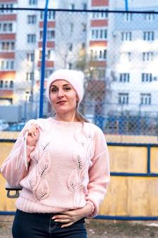 Bella donna indossata in maglione rosa e cappello con pattini da ghiaccio sul retro cammina nel parco innevato di inverno.