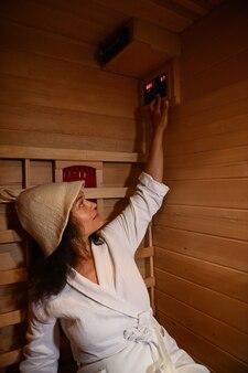 La bella donna che indossa un accappatoio e un cappello da sauna regola la temperatura nella sauna a infrarossi