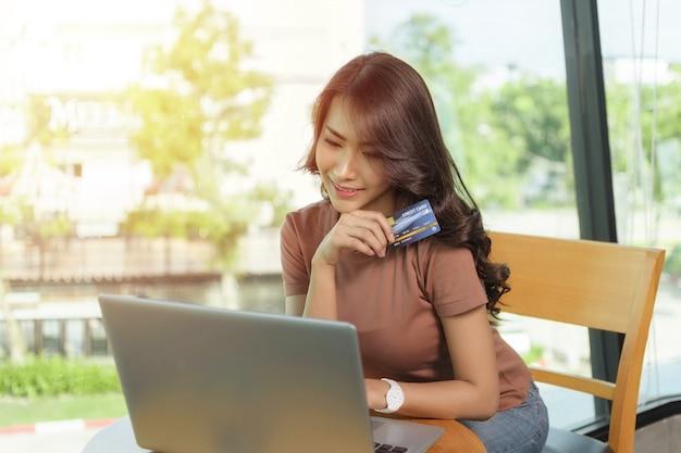 Bella donna che indossa una camicia marrone seduta e una faccia sorridente felice seduta da una grande finestra, sta facendo acquisti online con il computer portatile e tiene in mano una carta di credito.