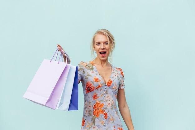 Bella donna che indossa un abito con borse della spesa su sfondo blu. concetto di acquisti e vendite