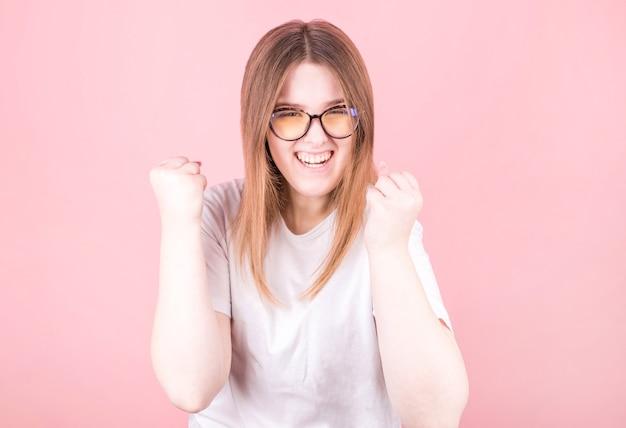 La bella donna con gli occhiali è felice ed entusiasta di esprimere un gesto di vittoria. vittoria riuscita e trionfante, trionfante, aperta