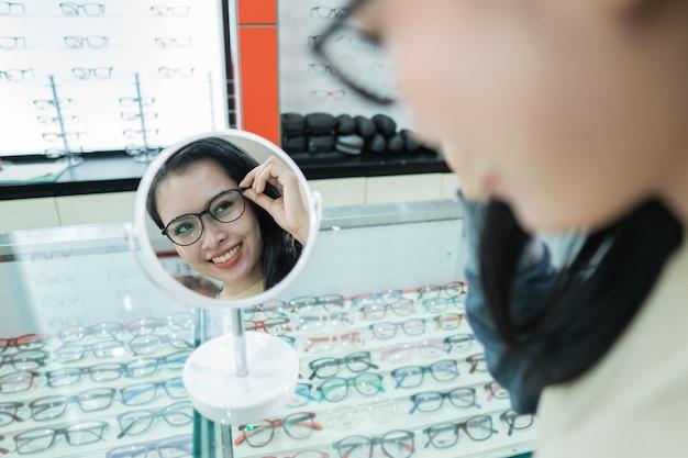 Una bella donna che indossa occhiali che sono stati selezionati in una clinica oculistica con uno sfondo di finestra di visualizzazione degli occhiali