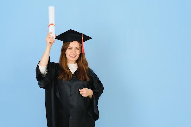 Bella donna che indossa il berretto di laurea e l'abito da cerimonia in possesso di laurea che sembra positivo e felice in piedi e sorride con un sorriso fiducioso.