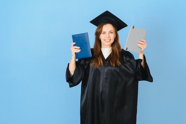 Bella donna che indossa il cappello di laurea e abito da cerimonia in possesso di laurea in piedi positivo e felice e sorridente con un sorriso fiducioso.