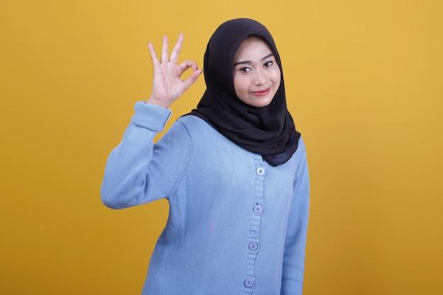 Bella donna che indossa l'hijab con dire ok sguardi felicemente espressione