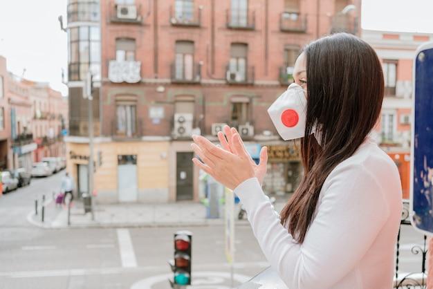 Bella donna che indossa una maschera di protezione e che applaude sul balcone