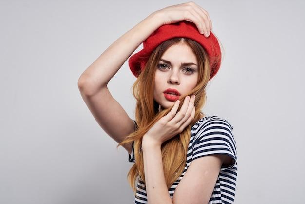 Bella donna che indossa un cappello rosso trucco francia europa moda posa modello studio