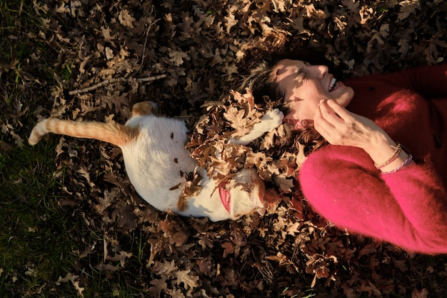 Bella donna che indossa un maglione rosso sdraiato sulle foglie di autunno che giocano con il suo animale domestico.