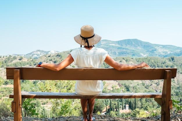 Bella donna che indossa il cappello di paglia che guarda verso le montagne