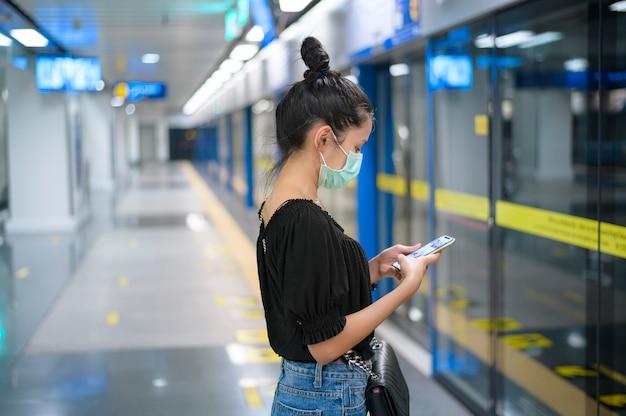 Una bella donna che indossa una mascherina chirurgica utilizzando il telefono mentre aspetta un treno in metropolitana, tecnologia e concetto covid19