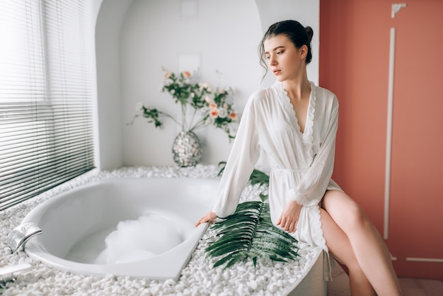 Bella donna in accappatoio bianco che si siede sul bordo della vasca da bagno con schiuma. interno bagno con finestra
