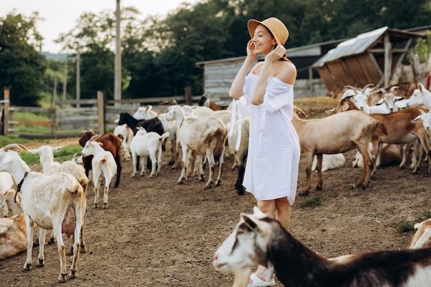Bella donna e vestito bianco e con un cappello beige tra le capre in una fattoria ecologica
