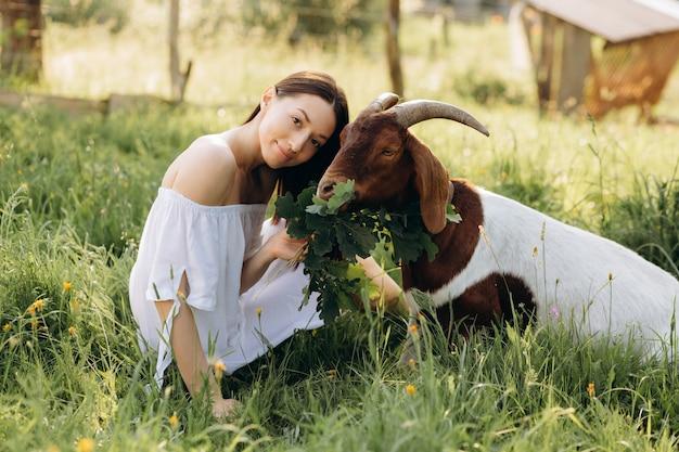 La bella donna in un vestito bianco alimenta la capra in una fattoria ecologica.