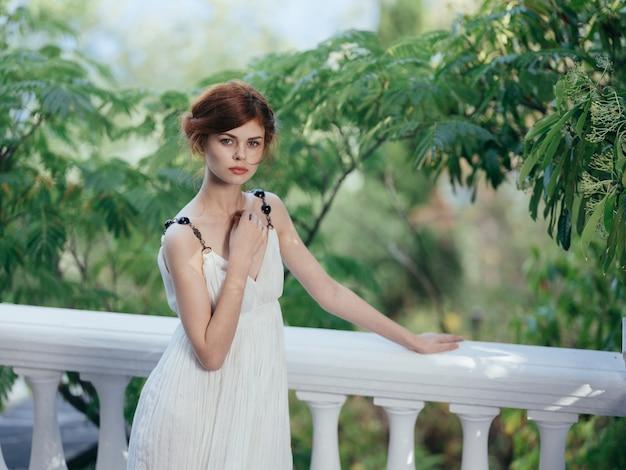 Bella donna in abito bianco foglie verdi mitologia grecia
