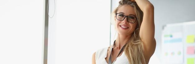 Una bella donna con un vestito bianco sta in ufficio e tiene in mano documenti donna alla moda
