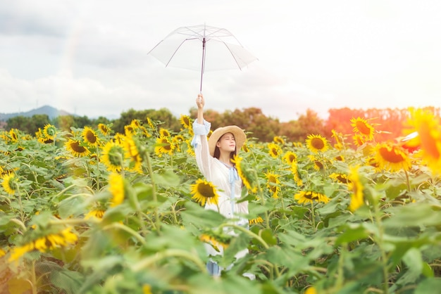 Bella donna in un abito bianco nel campo di girasoli