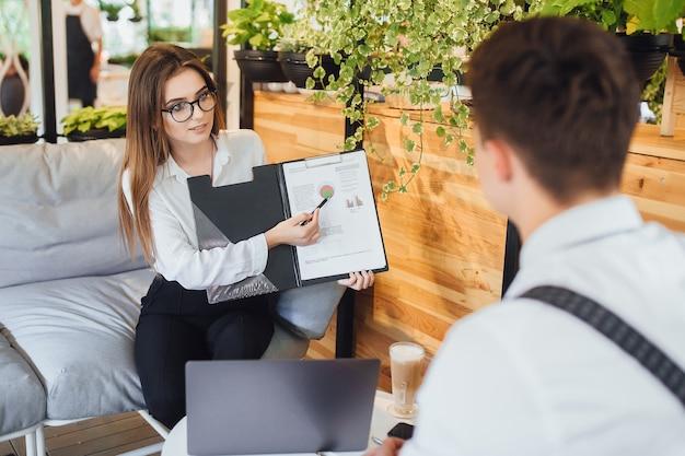 Bella donna in camicia bianca mostra i grafici per il suo capo, sulla terrazza estiva dell'ufficio moderno.