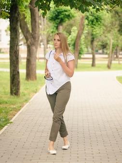 Una bella donna in camicia bianca con una borsa sulla spalla cammina nel parco cittadino.