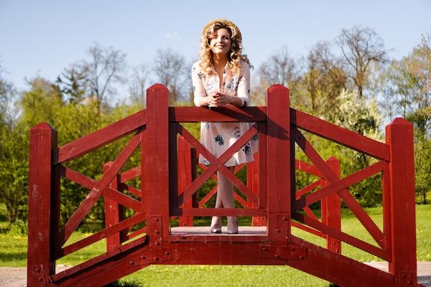 Bella donna in un abito estivo bianco e un cappello di paglia si trova su un ponte di betulle nel parco