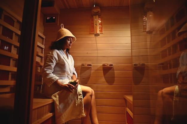 La bella donna in un accappatoio bianco della cialda ha cotto a vapore in una sauna. trattamento termale resort. concetti di terapia di bellezza