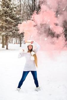 Bella donna in winter park che tiene bomba fumogena rossa