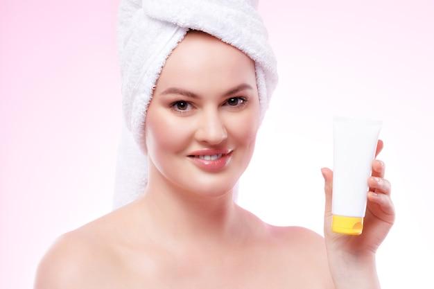 Bella donna con spalle nude e pelle perfetta che mostra un prodotto per la cura della pelle
