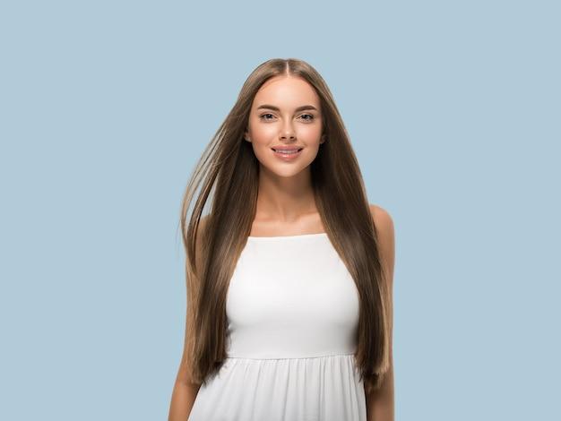 Bella donna con bei capelli lunghi e lisci volanti in abito bianco su sfondo colorato