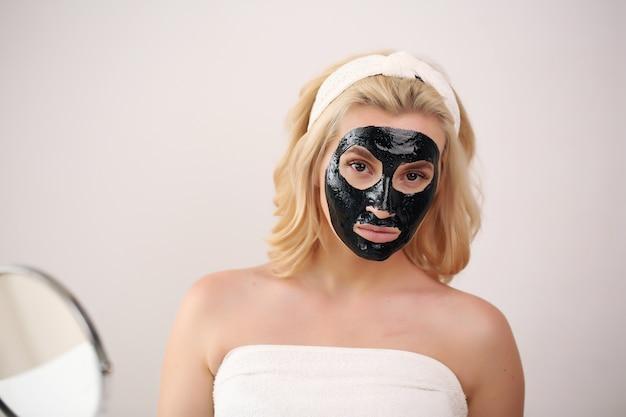 Bella donna con la pulizia nera maschera carbone nero sul viso.