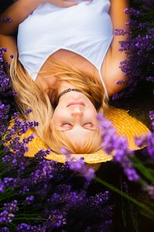 Bella donna con i capelli biondi è sdraiata nel campo di fiori di lavanda lavender