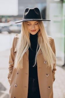 Bella donna con capelli biondi che indossa il cappello nero