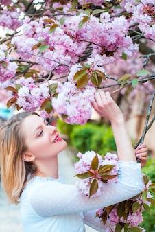 Bella donna con albero in fiore sakura e giornata di sole. fiore della margherita, fiori della margherita in fiore nel prato.