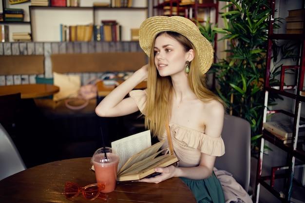 Bella donna con un libro nelle mani di uno stile di vita da caffè