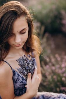 Bella donna con un mazzo di lavanda in mano in estate. avvicinamento.