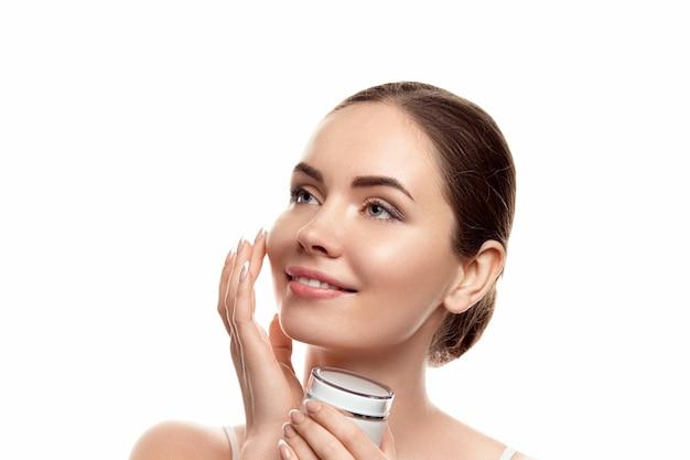 Bella donna con la pelle pulita. cura della pelle. cosmetici. trattamento facciale. crema idratante. cosmetologia, bellezza e spa