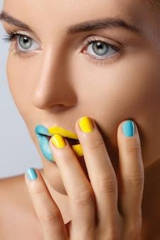 Bella donna con unghie e labbra colorate