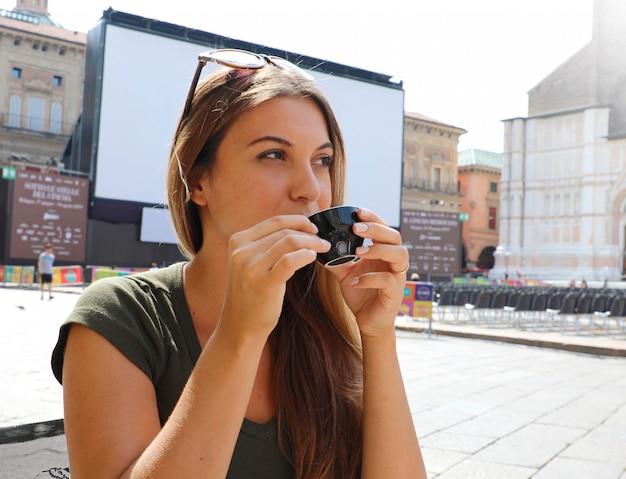 Bella donna con una tazza di caffè sul soleggiato paesaggio italiano