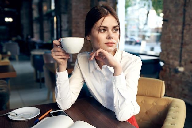 Bella donna con una tazza in mano si siede a un tavolo in un caffè e prenota