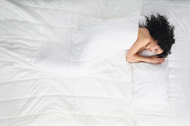 Bella donna con i capelli ricci dormire dolcemente nel letto coperto di coperta.